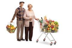Mari supérieur et épouse posant avec un caddie et un panier à provisions avec la nourriture images libres de droits