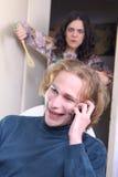 Mari téléphonant, épouse fâchée Image libre de droits
