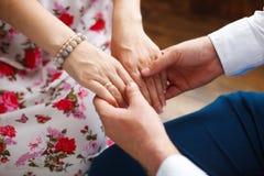 Mari tenant des mains de son épouse enceinte, plan rapproché Photos stock