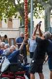 People taking photos of a hanging bunch of tomatoes during Tomato `Ramellet` Night Fair in Maria de la Salut royalty free stock images