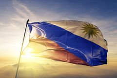 Maria Trinidad Sanchez Province of Dominican Republic flag textile cloth fabric waving on the top sunrise mist fog. Beautiful stock images