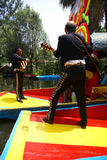 Mariachi guitar players on drifting barges Royalty Free Stock Images