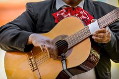 Mariachi playing acoustic guitar during the day. Male mariachi playing a wooden acoustic guitar during the day with hands royalty free stock photography