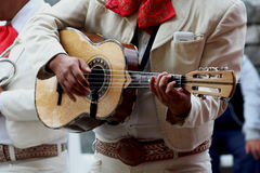 Mariachi playing guitar. A mexican mariachi playing his little handmade guitar in a local celebration in mothers day Royalty Free Stock Photography