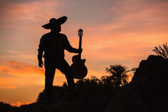 Mariachi silhouette on sunset background. Mexican musician mariachi with a guitar. Silhouette on sunset background stock photos