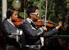 Mariachi Violinists. Young people celebrate Cinco De Mayo with a Mariachi band with a cool dude in shades playing the violin Stock Photos