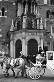 Mariacki Church in Cracow. Black and white image of the facade of Mary`s Church Mariacki in Cracow Krakow, Poland with horse carriage and tourists Royalty Free Stock Photography