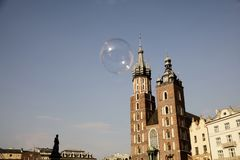Mariacki Church in Cracow. Mariacki or Mary`s Church in Cracow in Poland and soap bubble flying in the air Royalty Free Stock Photo