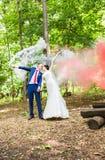 Mariage, amour, relations, mariage Nouveaux mariés de sourire et fumée colorée Photographie stock