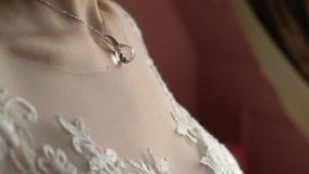 mariage bijou La jeune mariée dans une robe blanche mettant sur un collier autour de son cou banque de vidéos