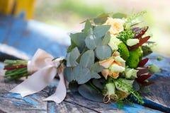 Mariage, bouquet des fleurs la jeune mariée avec des anneaux d'or Décorums Photographie stock