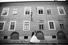 Mariage dans la ville historique Un couple étreignant la rue Verticale de la mari?e et du mari? image libre de droits