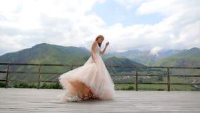mariage Danse rousse heureuse de jeune mariée dans la perspective des montagnes banque de vidéos