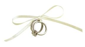 Mariage et bagues de fiançailles attachés avec le ruban en soie blanc Photos stock