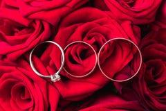 Mariage et bagues de fiançailles sur les roses rouges épousant le bouquet Images stock