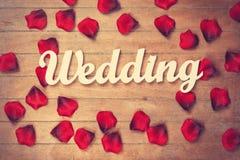 Mariage et pétales de Word sur la table en bois Image stock