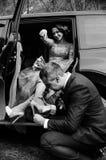 Mariage heureux, beau jeune couple heureux de jeunes mariés posant le soin près de la grande automobile noire Voiture noire de co image stock