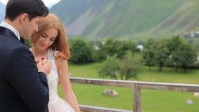 mariage Les nouveaux mariés heureux sont dans l'amour et la tendresse Couples affectueux à l'arrière-plan des montagnes banque de vidéos