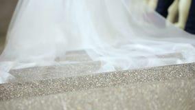 Mariage rêveur, belle jeune mariée, descendant des escaliers dans la robe impeccable avec des fleurs derrière banque de vidéos