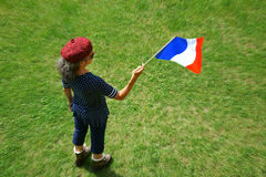 Marianne with Tricolor Flag. A woman wearing a beret is standing on a lawn and holding a French flag in one hand Royalty Free Stock Image