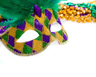 Marid Gras Mask and beads on white. A purple, gold and green mardi gras mask and beads on white