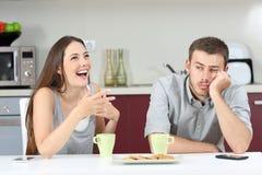 Marido aburrido que oye su hablar de la esposa imágenes de archivo libres de regalías
