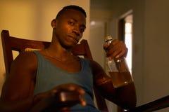 Marido bebido bebendo do álcool do homem negro do retrato em casa Imagens de Stock
