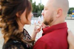 Marido calvo que lleva el baile rojo de la camisa con la esposa y que bebe el vino imagenes de archivo