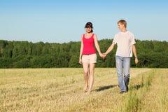 Marido, caminhada das mãos da terra arrendada da esposa no campo Imagens de Stock