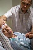 Marido cariñoso que toma cuidado de la esposa enferma foto de archivo libre de regalías