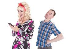 Marido celoso que mira a su esposa que usa el teléfono móvil fotos de archivo libres de regalías