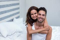 Marido de abarcamiento de la esposa en cama en casa Imagen de archivo
