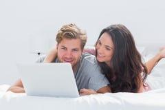 Marido de abarcamiento de la mujer mientras que usa un ordenador portátil Fotografía de archivo libre de regalías