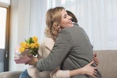 Marido de abarcamiento femenino de emisión con los presentes Imágenes de archivo libres de regalías