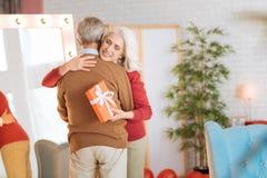 Marido de abarcamiento de la señora mayor feliz después de recibir el regalo Foto de archivo libre de regalías
