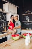 Marido de inquietação que beija a esposa grávida ao cozinhar o jantar imagens de stock royalty free