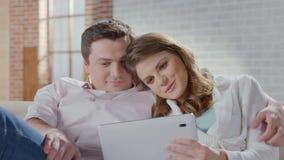 Marido de sorriso da esposa que compra em linha, escolhendo artigos na tabuleta filme
