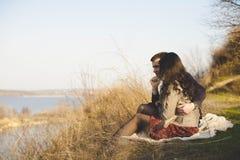 Marido e esposa na costa do lago com costas rochosas, mola adiantada Silhuetas dos amantes que entram na água na parte traseira Imagem de Stock Royalty Free