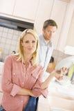 Marido e esposa que fazem pratos fotografia de stock