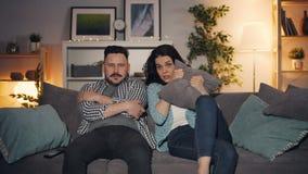 Marido e esposa que olham o filme assustador na tevê que olha a câmera com caras assustados
