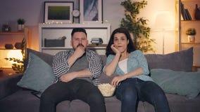Marido e esposa que olham a tevê em casa e que comem a pipoca tarde na noite junto