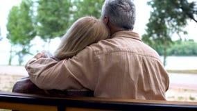 Marido envejecido que cuida que abraza a la esposa, sentándose en banco de parque, dulzura de las relaciones imágenes de archivo libres de regalías