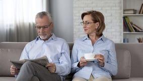 Marido envejecido y esposa que se sientan en el sofá, periódico de la lectura del hombre, té de consumición de la mujer fotos de archivo libres de regalías