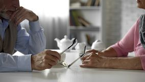 Marido envejecido y esposa que tienen conflicto que se sienta a través de la tabla sobre la taza de té fotografía de archivo libre de regalías