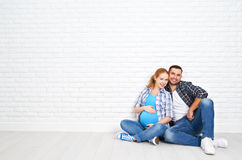 Marido feliz de los pares y esposa embarazada cerca de la pared de ladrillo en blanco Fotos de archivo libres de regalías