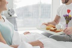 Marido feliz que trata a su esposa con el desayuno romántico Imagenes de archivo