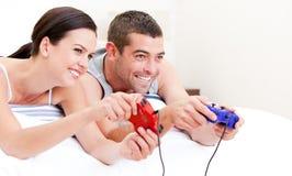 Marido feliz y esposa que juegan juegos de video en cama Imagen de archivo libre de regalías