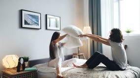 Marido juguetón y esposa que se divierten con lucha de almohada en la cama en casa que ríe almacen de metraje de vídeo