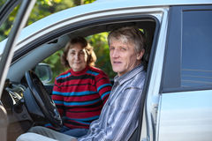 Marido maduro y esposa que se sientan en el vehículo de tierra, mirando a través de la puerta abierta Imagen de archivo libre de regalías