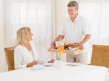 Marido mayor maduro sonriente que sirve a su esposa el desayuno sano Imagen de archivo libre de regalías